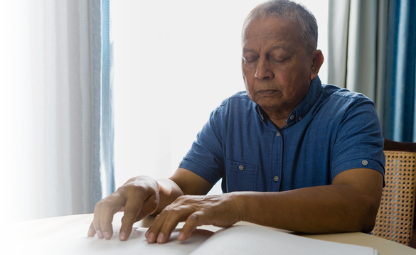 Image of a man reading braille text in a book
